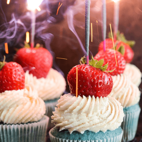 Red, White & Blue Sparkler Cupcakes topped with whole strawberry and a sparkler