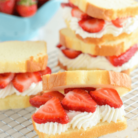 Strawberry Shortcake Sandwiches on a rack with sliced strawberries and whipped cream