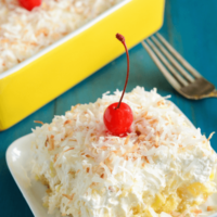Twinkie, Pineapple & Coconut No Bake Cake on a white plate topped with shredded coconut and a cherry
