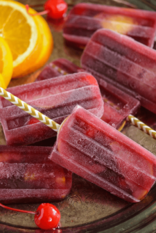 Sangria Popsicles with oranges and cherries on white and gold popsicle sticks on a serving tray