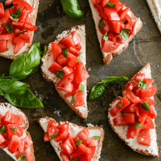 Tomato & Goat Cheese Toasts on a dark surface