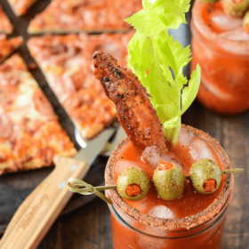Bacon Bloody Mary with bacon, a celery stalk, and green olive skewers - pizza is shown in the background