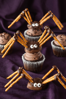 Two Pretzel Spiders on Top of Cupcakes and One on its Own on Top of a Purple Tablecloth