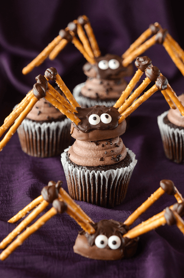 Three Chocolate Pretzel Spiders Being Displayed Over a Purple Sheet