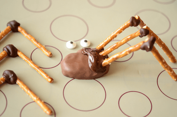 Three Pretzel Legs Attached to a Pumpkin Reese's with Melted Chocolate