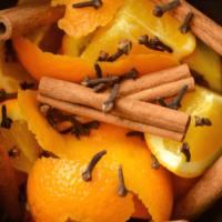 Cinnamon Orange Potpourri in a slow cooker crock with cloves, cinnamon sticks, and oranges
