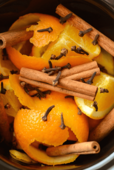 Cinnamon Orange Potpourri in a slow cooker crock with cloves, cinnamon sticks, and oranges