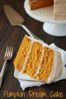Slice of Pumpkin Dream Cake on a white plate. Full cake in the background.