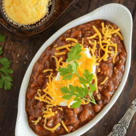 Slow Cooker Bean Chili and Easy Cornbread Muffins in an oval casserole dish