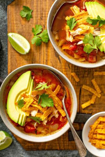 Chicken Tortilla Soup in bowls with avocado.