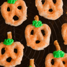 White chocolate covered Pumpkin Pretzels on a dark surface