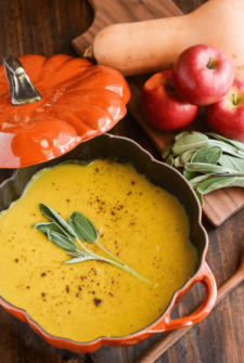Butternut Squash, Apple & Sage Soup topped with sage in a pumpkin dish with a wooden spoon