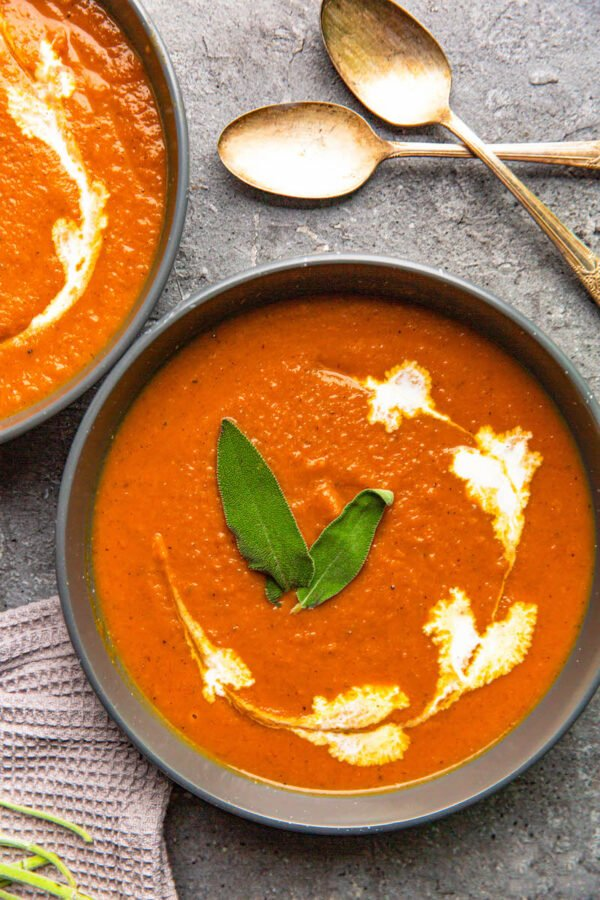 Butternut squash soup in a bowl with cream and sage on top.