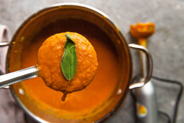 Squash soup in a pot with a ladle scooping some out with sage on top.