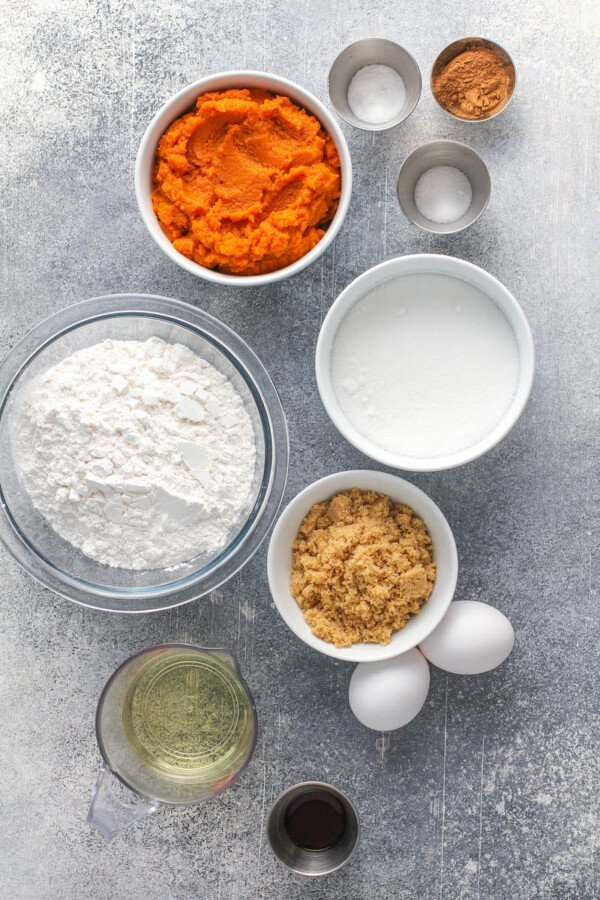 Ingredients for pumpkin muffins in bowls on a gray background.