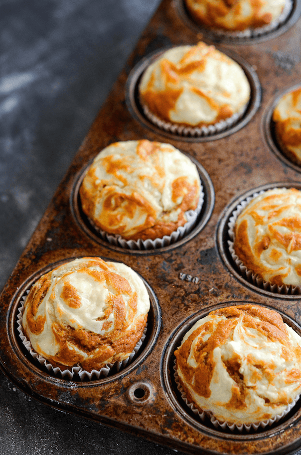 Pumpkin Cream Cheese Swirl Muffins in a muffin pan.