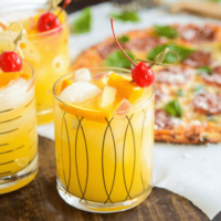 Sparkling Autumn Spiced Sangria topped with a cherry and orange skewer with a pizza in the background