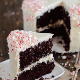 Slice of Chocolate Peppermint Dream Cake covered in crushed peppermint on a white plate with a fork