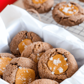 Chocolate cookies with a caramel center and salt on top in a white container