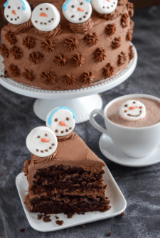 Slice of Hot Chocolate Dream Cake with Snowmen marshmallows and a cup of hot chocolate