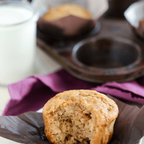 Banana Brown Sugar Muffins with a bite taken out of one with a glass of milk in a clear glass