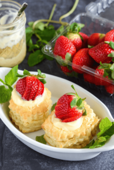 Berries & Cream in Puff Pastry in a white dish topped with fresh strawberries