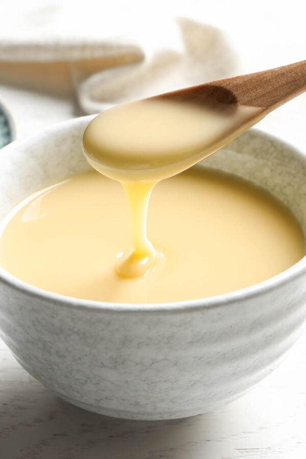Sweetened condensed milk in a bowl with a spoon.