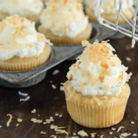Triple Coconut Poke Cupcakes piled high with whipped cream and shredded coconut