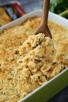 Baked Cauliflower Mac & Cheese in a green casserole with a wooden spoon scooping out of dish