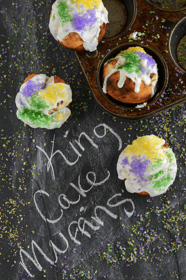 Top view of cinnamon roll muffins with icing with purple, green and yellow sprinkles on top on a chalkboard surface