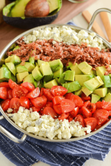 Copycat Maggianos Chopped Salad - blue cheese, tomatoes, avocados, bacon in a silver serving dish on a blue and white cloth