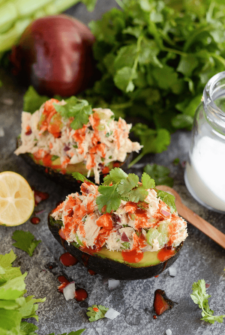 Mexican Tuna Salad Stuffed Avocados topped with hot sauce and cilantro