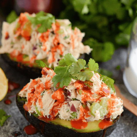 Close up of an avocado stuff with tuna salad and topped with hot sauce and cilantro
