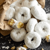 A Pile of Homemade Doughnuts Covered in Confectioner's Sugar with a Paper Bag Holding Additional Doughnuts