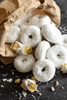 Bag of Mini Powdered Doughnuts on a dark surface
