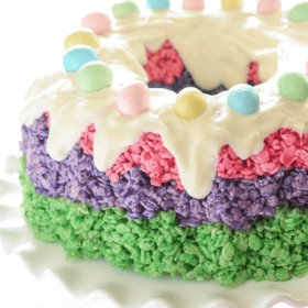 Easter Rice Krispie Cake topped with icing and robin's eggs on a white cake stand
