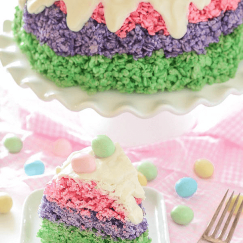 Slice of Easter Rice Krispie Cake topped with icing and robin's eggs with remaining cake on a white cake stand
