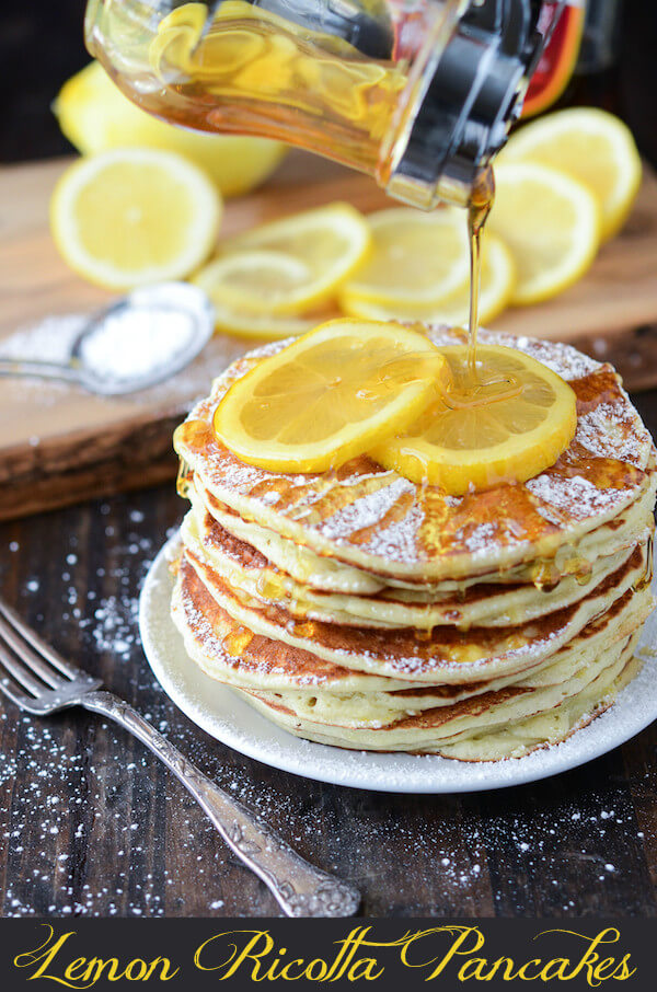 Fluffy Lemon Ricotta Pancakes topped with powdered sugar, lemon slices, and drizzled with sugar