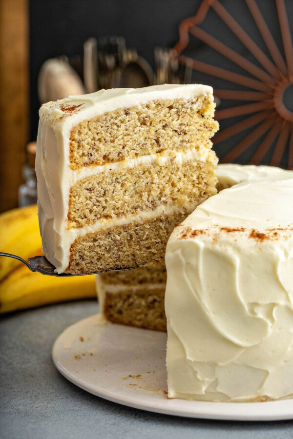A slice of the best banana cake recipe being lifted away form the whole cake with a cake server.