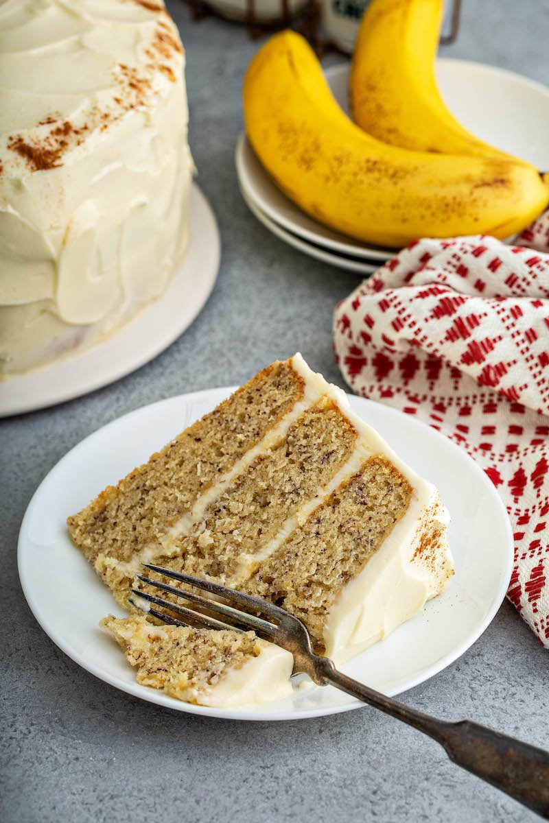 Slice of banana cake with a fork on a plate.