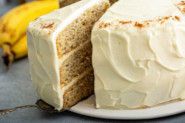 Up close image of a slice of cake being pulled away from a whole cake with a cake server.