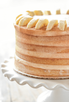 Close up of Banana Dream Cake with Cinnamon Icing on a white cake stand