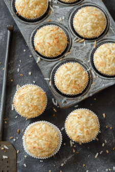 Coconut Banana Crunch Muffins in muffin tin and on a dark surface