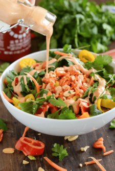 Spicy Thai Salmon Chopped Salad with Sriracha Peanut Dressing drizzled over salad in a white bowl
