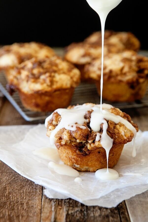 A Cinnamon Roll Muffin Being Drizzled with Icing