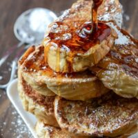 A Stack of Cuban Bread French Toast with Syrup Drizzled on Top