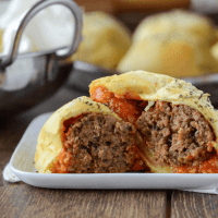 Meatball Bombs cut in half showing meatball with sauce on a white plate