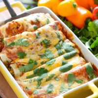 Enchiladas in casserole dish being scooped up with a spatula.
