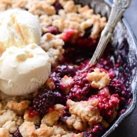 Skillet Berry Cobbler in a cast iron skillet topped with crumble and vanilla ice cream
