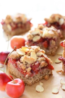 Close up of a Gluten Free Cherry Almond Bar surrounded by cherries and nuts
